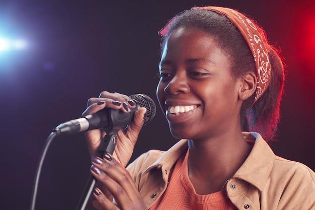 Bliska portret uśmiechniętej kobiety african-american śpiewającej do mikrofonu, stojąc na scenie, kopia przestrzeń