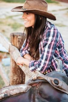 Bliska portret uśmiechniętej szczęśliwej kowbojki opartej na płocie na ranczo