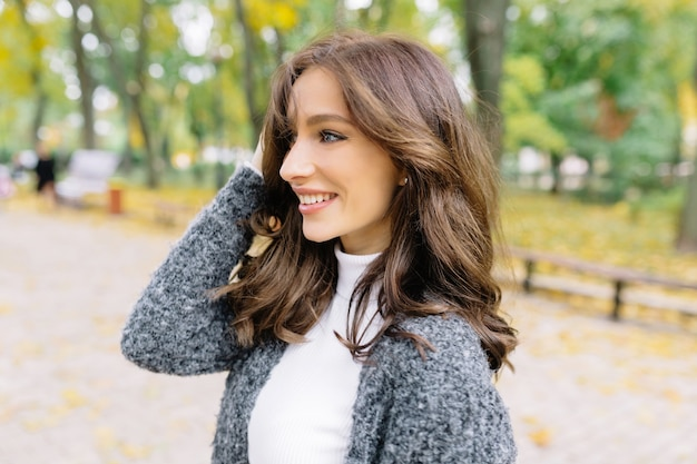 Bliska portret w profilu wrażliwej kobiety. ma ciemne, krótkie włosy i cudowne, duże niebieskie oczy. w zielonym parku.