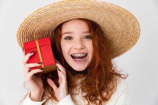 Bliska portret wesoła młoda nastolatka ubrana w letni kapelusz stojący na białym tle nad białym tle, pokazując obecne pole