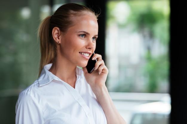Bliska portret wesołej młodej bizneswoman stojącej i rozmawiającej przez telefon komórkowy na zewnątrz