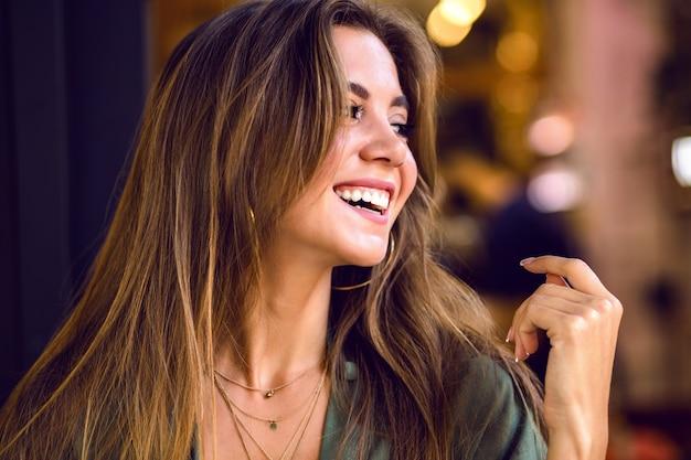 Bliska portret wspaniały młody zmysłowy model z długimi brązowymi włosami i nieśmiały ładny uśmiech, naturalne czyste piękno, miękki makijaż.
