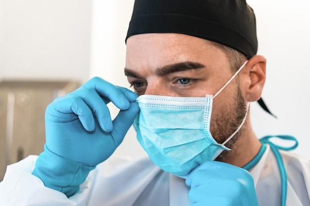 Bliska portret z twarzą młodego lekarza chirurga noszącego maskę medyczną