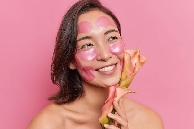 Bliska portret zadowolonej młodej azjatyckiej kobiety z uśmiechem zębów cieszę się, że kwiat nakłada hydrożelowe łaty na twarz, aby odświeżyć skórę, stoi bez koszuli na różowej ścianie