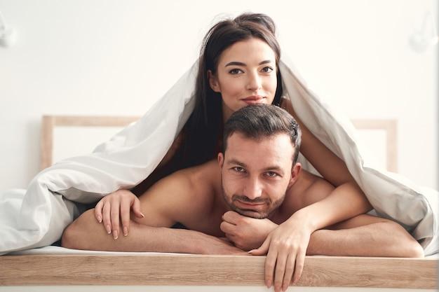 Bliska portret zadowolonej nowo poślubionej młodej pary rasy kaukaskiej pod kocem patrząc w przyszłość .