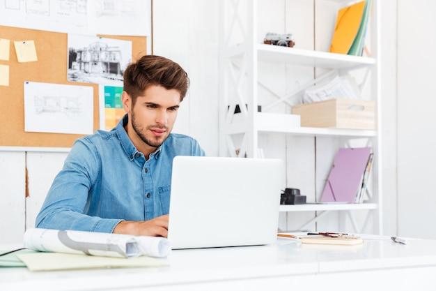 Bliska portret zamyślonego młodego biznesmena dorywczo za pomocą laptopa w biurze