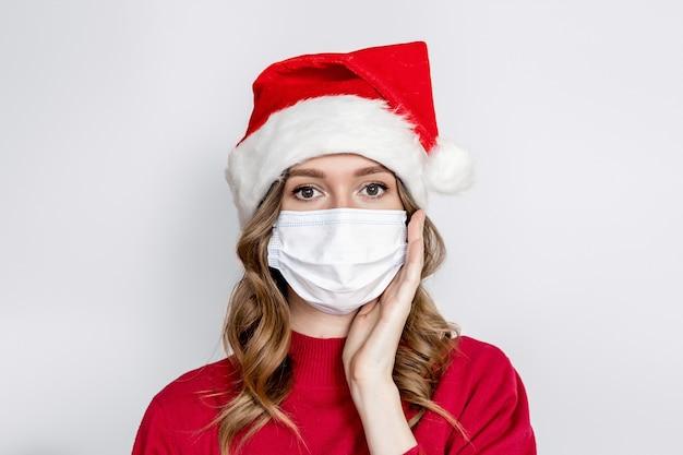 Bliska portret zaskoczony dziewczynka kaukaski trzymając rękę w twarz na sobie maskę medyczną i kapelusz santa na białym tle studio. ochrona przed zarazkami i wirusami w nowym roku