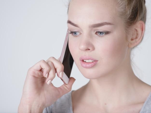Bliska portret zdenerwowanej kobiety rozmawia przez telefon komórkowy na szarym tle