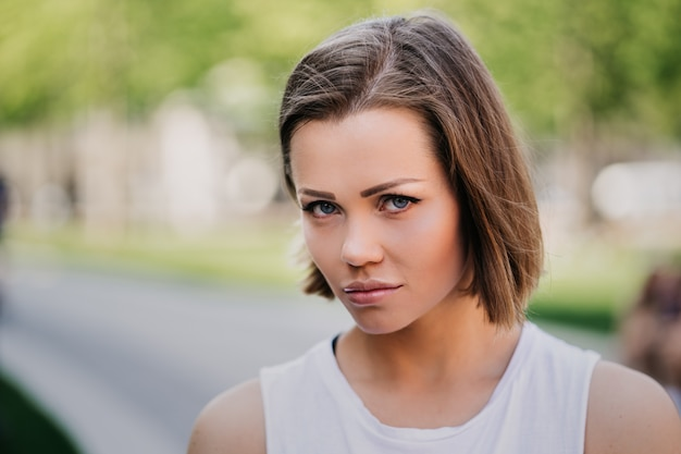Bliska portret zdenerwowanej młodej damy z krótkimi włosami ubranej w białą koszulkę, idzie sama w parku, zerwała ze swoim chłopakiem. ludzie emocji i relacji.