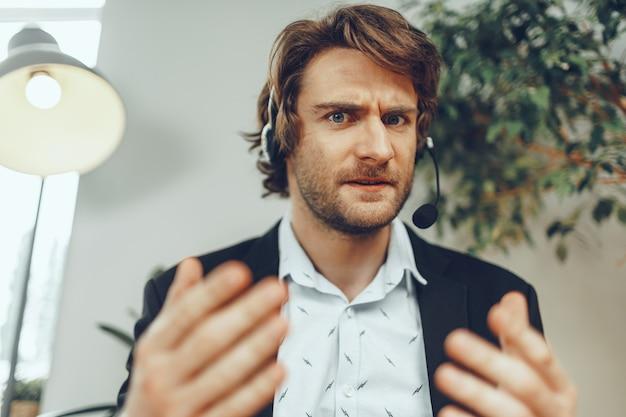 Bliska portret zły biznesmen z zestawem słuchawkowym o stresującej rozmowy online