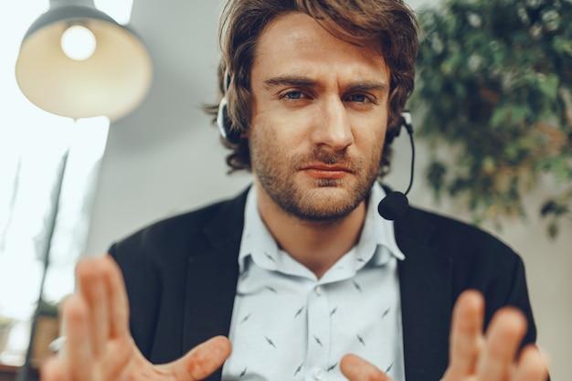 Bliska portret zły biznesmen z zestawem słuchawkowym