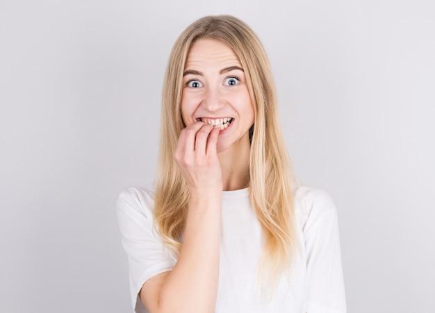 Bliska portret zmartwiona blondynka w białej koszulce gryząc paznokcie na białym tle