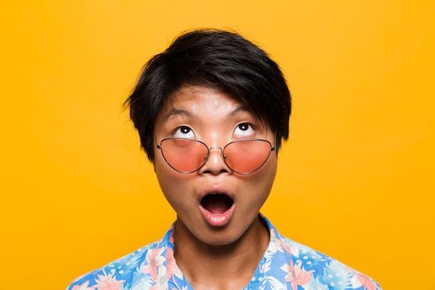 Bliska portret zszokowanego azjatyckiego mężczyzny w okularach przeciwsłonecznych