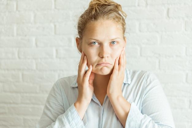 Bliska poważna zdenerwowana kobieta dotyka jej twarzy obiema rękami, patrząc w kamerę