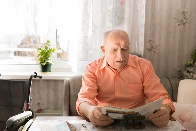 Bliska poważny stary łysy człowiek czyta gazetę przy stole w salonie.