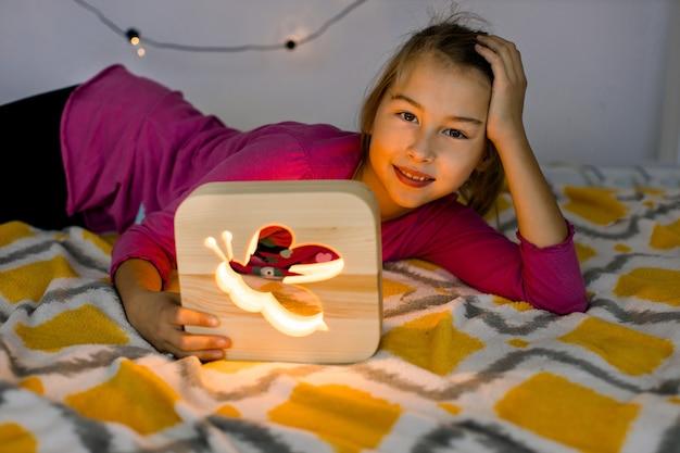Bliska poziome ujęcie szczęśliwej uśmiechniętej 10-letniej dziewczynki, leżącej na wygodnym łóżku, trzymając piękną drewnianą lampkę nocną ze zdjęciem pszczoły.