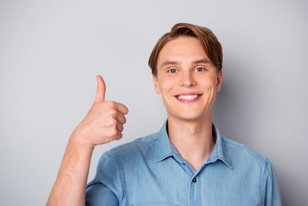 Bliska pozytywnego, wesołego faceta poleca doskonałe reklamy promocyjne pokazujące kciuk w górę, nosić nowoczesny strój odizolowany na szarej ścianie
