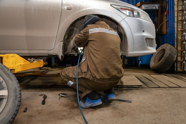 Bliska profesjonalny mechanik samochodowy zmienia koło samochodu w auto serwis. autoworker dokonuje wymiany opony lub koła w garażu stacji naprawczej
