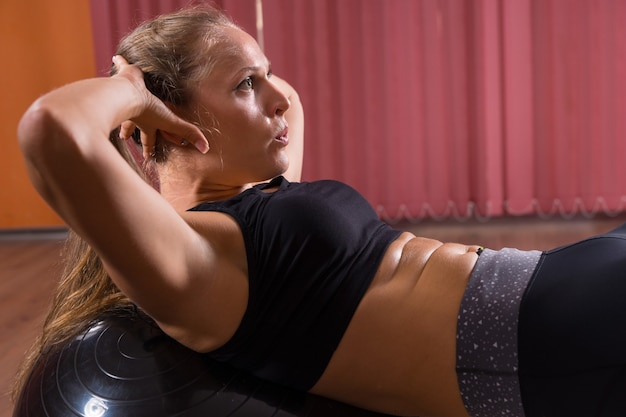 Bliska profil boczny skupiona młoda blond kobieta ubrana w odzież do ćwiczeń robi brzuszki brzucha za pomocą nadmuchiwanej piłki do ćwiczeń w studio tańca