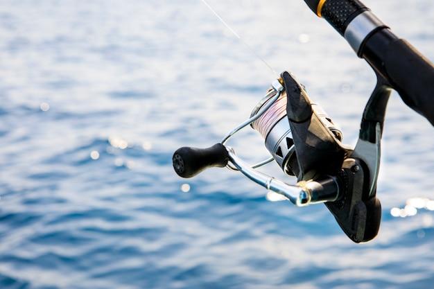 Bliska przędzenia wędka na tle błękitnej wody morskiej