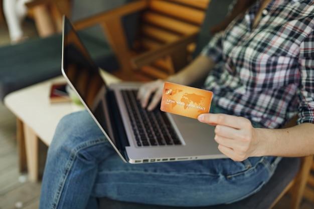Bliska przycięta dziewczyna na zewnątrz ulicy kawiarnia drewniana kawiarnia siedząca, pracująca na komputerze typu laptop, przytrzymaj bankową kartę kredytową relaks w czasie wolnym