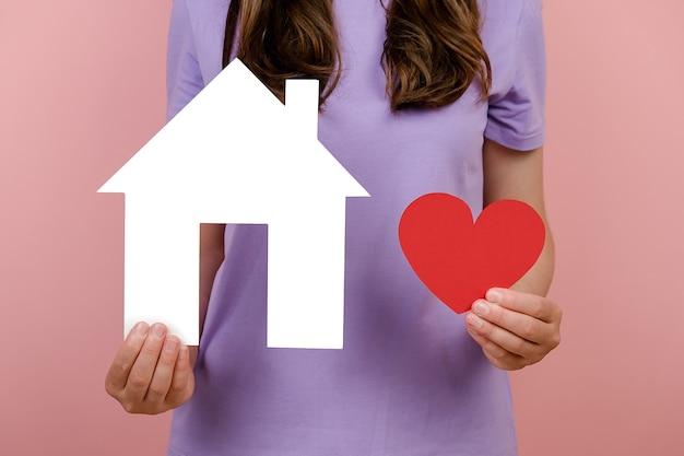 Bliska przycięta młoda kobieta nosi t-shirt pokazuje mały biały papierowy dom i małe czerwone serce, odizolowane na różowym tle w studio. koncepcja kochającego, chroniącego, przytulnego domu, walentynki