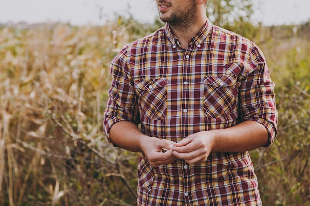 Bliska przycięte młody nieogolony mężczyzna w kraciastej koszuli odwrócił głowę i trzyma przynętę larw do łowienia ryb na tle krzewów i trzcin. styl życia, rekreacja rybaka, koncepcja wypoczynku.