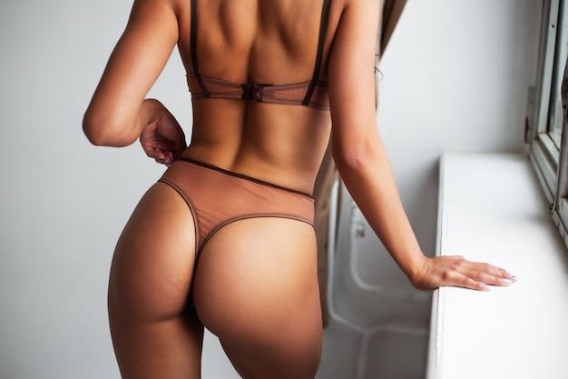 Bliska przycięte zdjęcie dziewczyny w beżowym bikini z dużym tyłkiem na białym tle romantyczny luksus