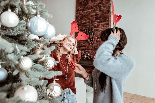 Bliska przyjaźń. dziecinne śmieszne dziewczyny tańczą i wygłupiają się razem przy udekorowanej choince