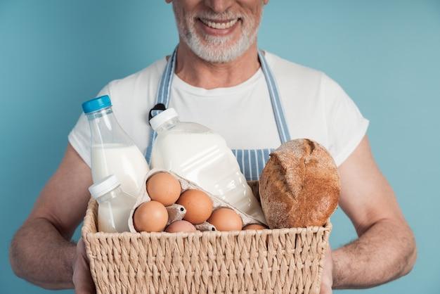 Bliska przystojny, od lat starszy mężczyzna trzyma kosz z jedzeniem, chleb, mleko, jajka
