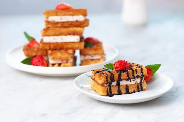 Bliska pszenny gofr belgii zwieńczony czekoladą i ozdobiony posiekanymi truskawkami