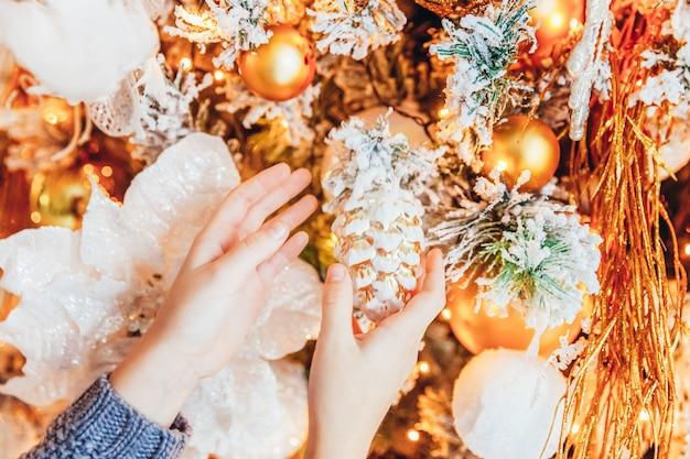 Bliska ręce dziewczyny dekorowanie choinki