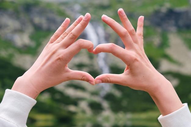 Bliska ręce kobiety przedstawiające serce wodospadu i przejrzystą, czystą wodę jeziora z miejsca na kopię. powołanie w koncepcji gór. samotność z naturą.