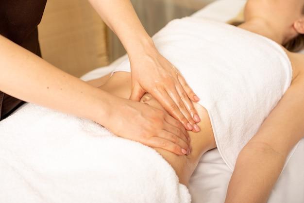 Bliska ręce kręgarza lub masażysty relaksujący masaż brzucha dla kobiety leżącej we wnętrzu kliniki. profesjonalny lekarz masażysta podczas pracy z pacjentem