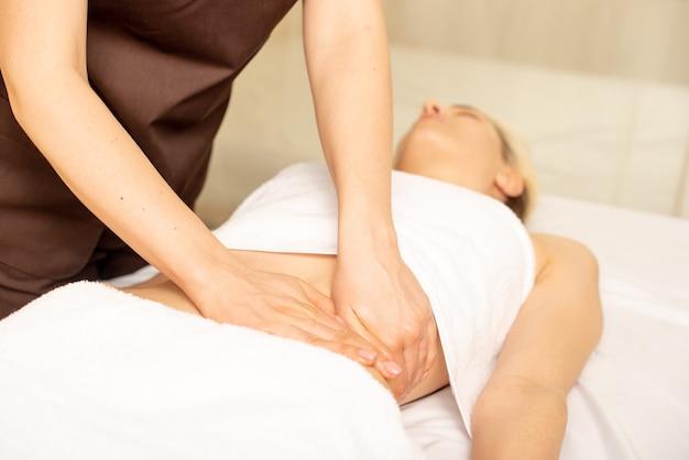 Bliska ręce kręgarza lub masażysty relaksujący masaż brzucha dla kobiety leżącej we wnętrzu kliniki.