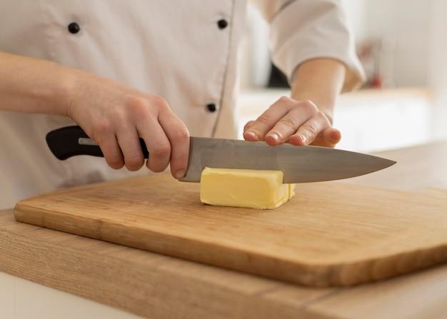 Bliska ręce krojenia masła