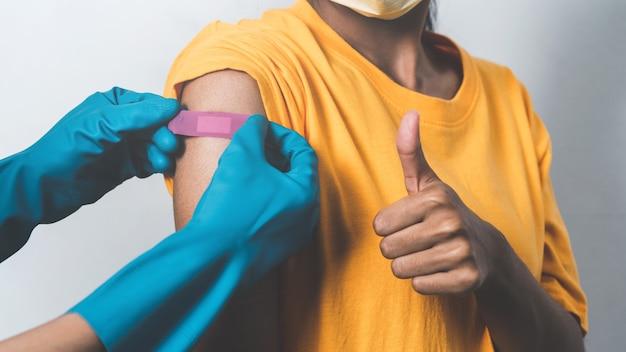 Bliska ręce lekarza z rękawicą kładzenia gipsu na ramieniu pacjentki po szczepieniu.