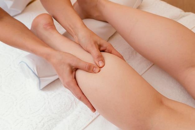 Bliska ręce masuje nogę