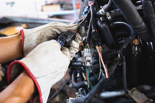 Bliska ręce mechanika samochodowego robi serwis samochodowy i konserwację. okablowanie samochodowe z wymianą adapterów i złączy.