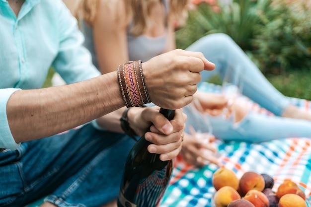Bliska ręce mężczyzny otwierającego wino musujące siedząc na kocu z żoną świętując życie, ciesząc się sobą
