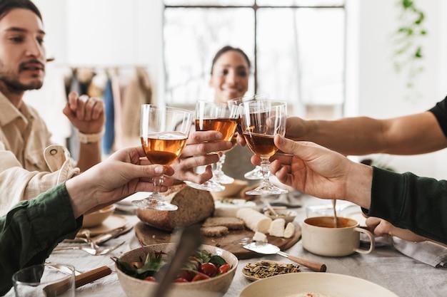Bliska ręce międzynarodowych przyjaciół trzymając kieliszki wina