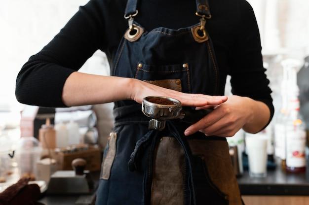 Bliska ręce przygotowując kawę