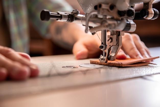 Bliska ręce rzemieślnika szyją puste rzeczy do użytku w portfelu maszyna do szycia pracująca w warsztacie skórzanym