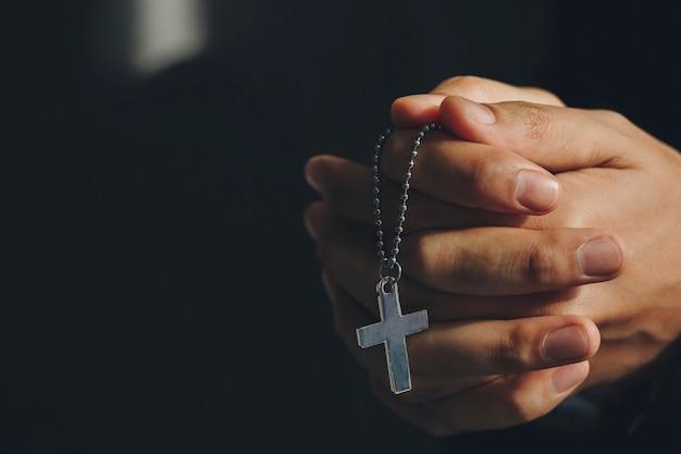 Bliska ręce trzyma krzyż naszyjnik. módlcie się o boże błogosławieństwo, aby życzyć sobie lepszego życia
