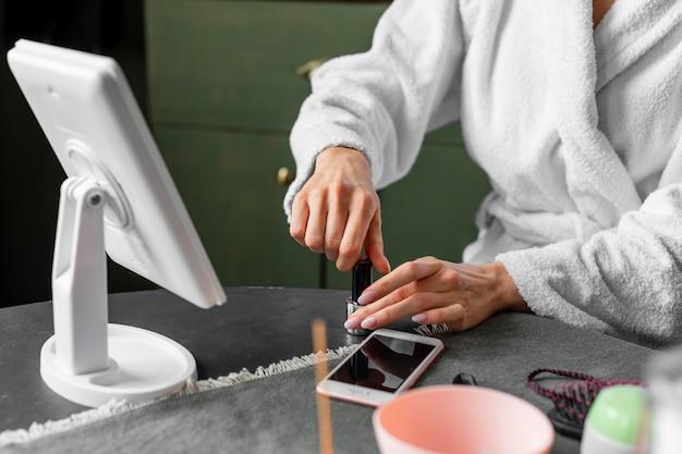 Bliska ręce trzymając butelkę lakieru do paznokci