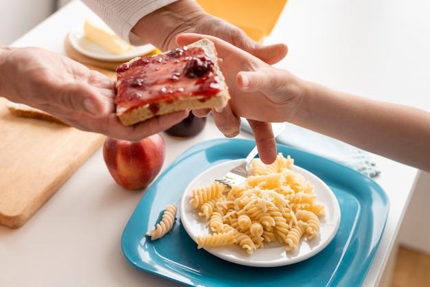 Bliska ręce trzymając chleb z dżemem
