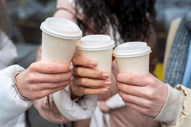 Bliska ręce trzymając filiżanki do kawy