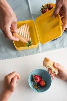 Bliska ręce trzymając kanapkę