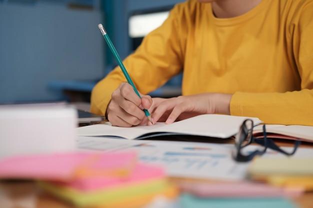 Bliska ręce z pisania piórem na notebooku. koncepcja edukacji.
