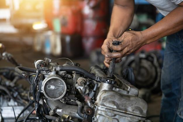 Bliska ręka atrakcyjnego człowieka ciężko pracuje i naprawić mechanik samochodowy na silniku samochodowym w garażu mechaniki. serwis naprawczy